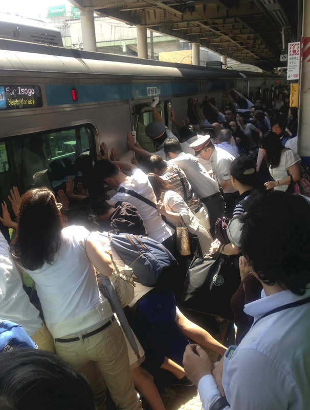 Train passengers and railway staff push a train car in their effort to rescue a woman who fell and got stuck between the car and the platform while getting off at Japan Railway Minami Urawa Station in Saitama, near Tokyo, Monday morning. A Yomiuri Shimbun photographer who happened to be there said there was a big applause when the woman, who fell to her waist, was safely rescued without any serious injuries. About 40 people helped the staff who were pushing the car after hearing an announcement that a passenger has been trapped.