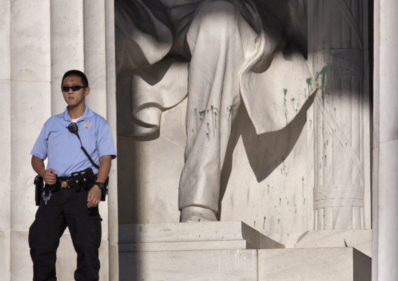 A U.S. Park Police officer stands guard next to the statue of Abraham Lincoln at the memorial in Washington on Friday after someone splattered green paint on the statue.