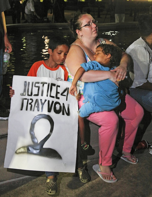In this Saturday, July 13, 2013 file photo, a mother holds and sits with her children after hearing the verdict of not guilty in the trial of neighborhood watch volunteer George Zimmerman at the Seminole County Courthouse, in Sanford, Fla. Zimmerman was cleared of all charges Saturday in the shooting of unarmed teenager Trayvon Martin, whose killing unleashed furious debate across the U.S. over racial profiling, self-defense and equal justice. Some view Zimmerman's acquittal as a blow to race relations. (AP Photo/Mike Brown, File)