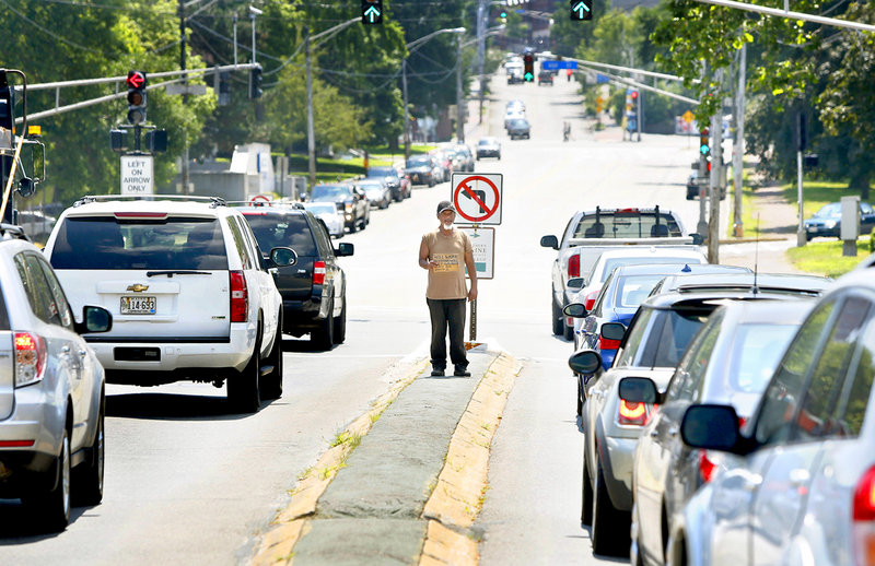 A man panhandles on a median on the corner of Marginal Way and Forest Avenue in Portland on July 16, 2013.