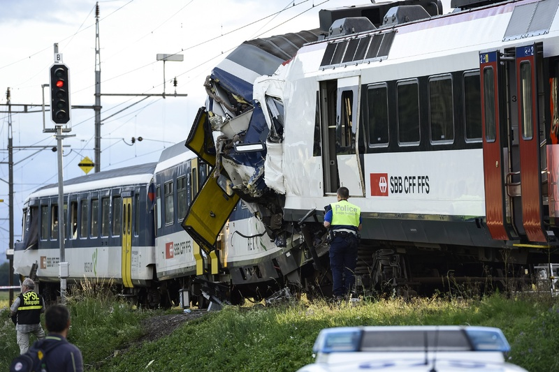 Police inspect the site where two passenger trains collided head-on in Granges-pres-Marnand, western Switzerland, on Monday.