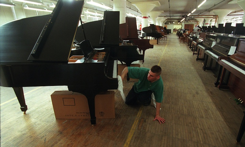 In a May 17, 1996 file photo, John Volastro, who works in the restoration department of Steinway and Sons, applies the finishing touches to a Steinway piano at piano maker's factory in the Queens Borough of New York. The famed piano maker Steinway is being acquired by private equity firm Kohlberg & Co. for about $438 million. Steinway, which has been in business for 160 years, said previously that was looking into selling the company. The board of the Waltham, Mass., company unanimously recommended Monday, July 1, 2013 that shareholders tender their stock. (AP Photo/Adam Nadel, File)