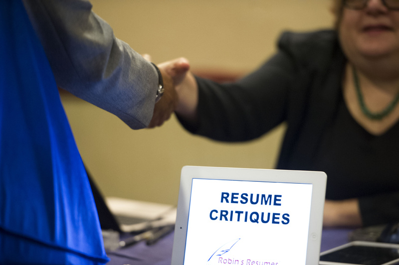 A job seeker stops at a table offering resume critiques during a job fair in Atlanta in May.