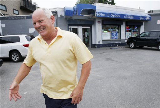 In this June 6, 2013, photo, Stephen Rakes greets an acquaintance outside the liquor store he once owned in the South Boston neighborhood of Boston. Authorities say Rakes, who was on the witness list for the racketeering trial of reputed mobster James