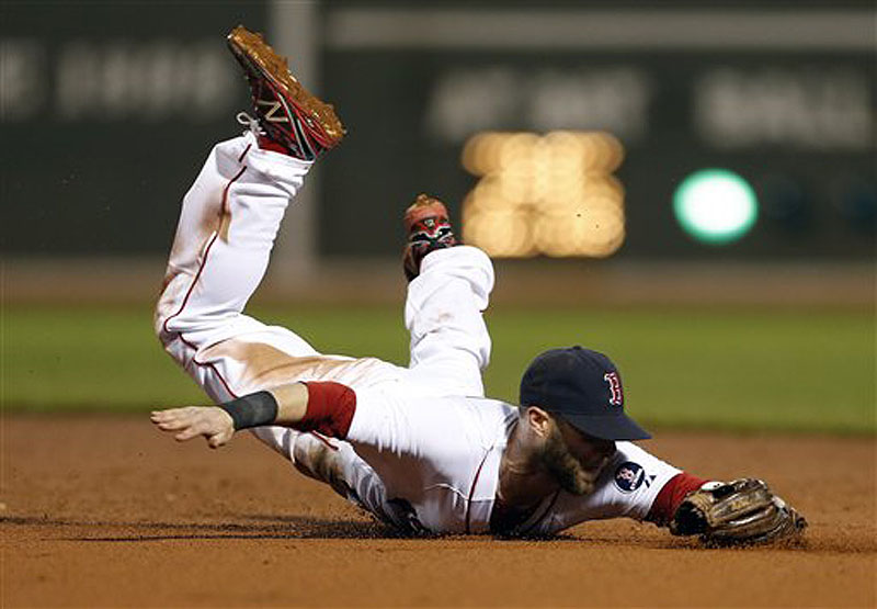 Boston's Dustin Pedroia dives for a line drive in the seventh inning against the New York Yankees in Boston on Sunday. The Red Sox won in the 11th, 8-7.