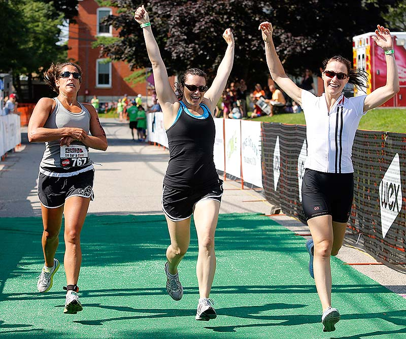 TriStrength team member Faye Maier of Scarborough stops the clock on her watch as teammates Kiely Foley of South Portland and Ellen Janokowski of Portland, right, celebrate their first-place finish in the survivors team competition Sunday in the Tri for a Cure in South Portland.
