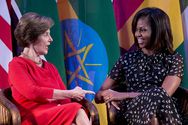 "U.S. first lady Michelle Obama, right, and former U.S. first lady Laura Bush talk each other as they participate in the African First Ladies Summit: ""Investing in Women: Strengthening Africa,"" hosted by the George W. Bush Institute, Tuesday, July 2, 2013, in Dar es Salaam, Tanzania. ("