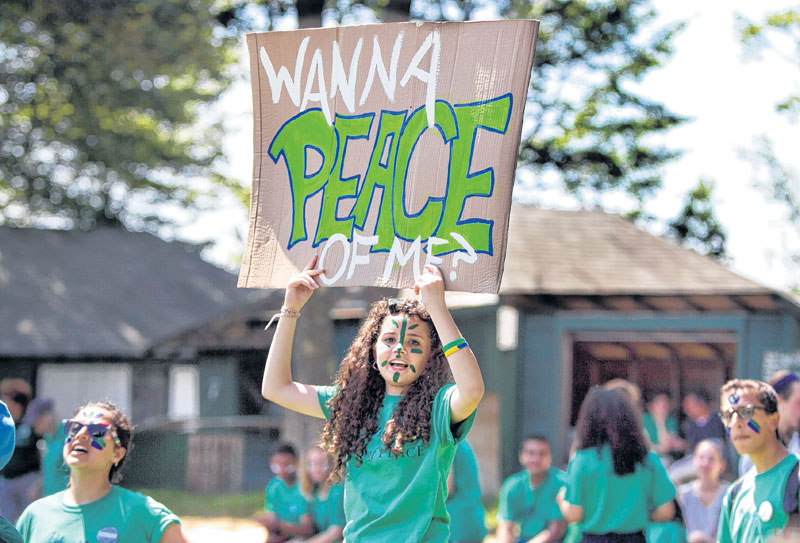 A camper displays a sign during a softball game at the Seeds of Peace camp in Otisfield on Friday.