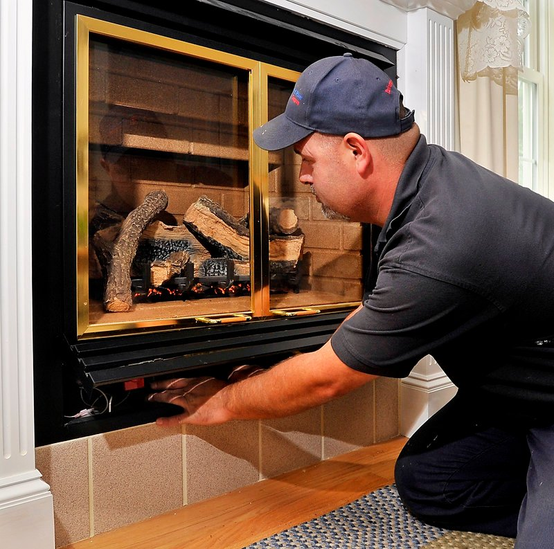 Mike Aboud, a service technician for Dead River Company, tests the prooane system for leaks and poor performance of a fireplace insert at a home in Scarborough on Friday, June 28, 2013.