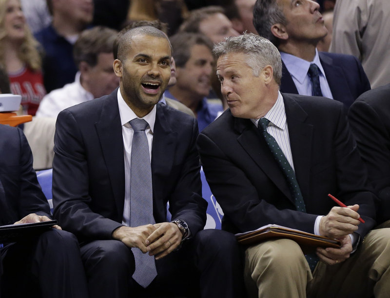 San Antonio Spurs' guard Tony Parker, left, sits with assistant coach Brett Brown during the second half of an NBA basketball game on March 6 in San Antonio.