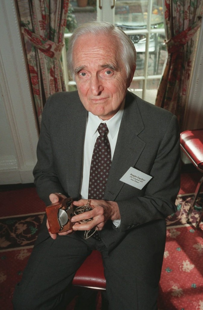 Doug Engelbart holds an early working model of his computer mouse. He patented the device in 1970 but never profited much from his invention.