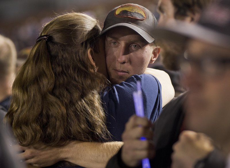 Firefighter Brendan McDonough embraces a mourner at a vigil in Prescott, Ariz., on Tuesday night. McDonough is the sole survivor of the Granite Mountain Hotshot Crew that perished in a raging wildfire Sunday. He was serving as a lookout and relaying key information to his colleagues when the fire trapped and killed them, officials said. McDonough, 21, was in his third season with the Hotshots.