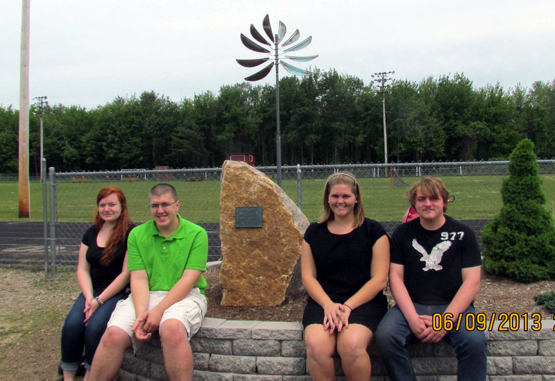 The officers of the Wells High School Class of 2012, from left, Logan Snyder, secretary; Michael Valente. treasurer; Whitney Lallas, president; and Connor Sweatt, vice-president, posing with their class gift, the sculpture in the background.