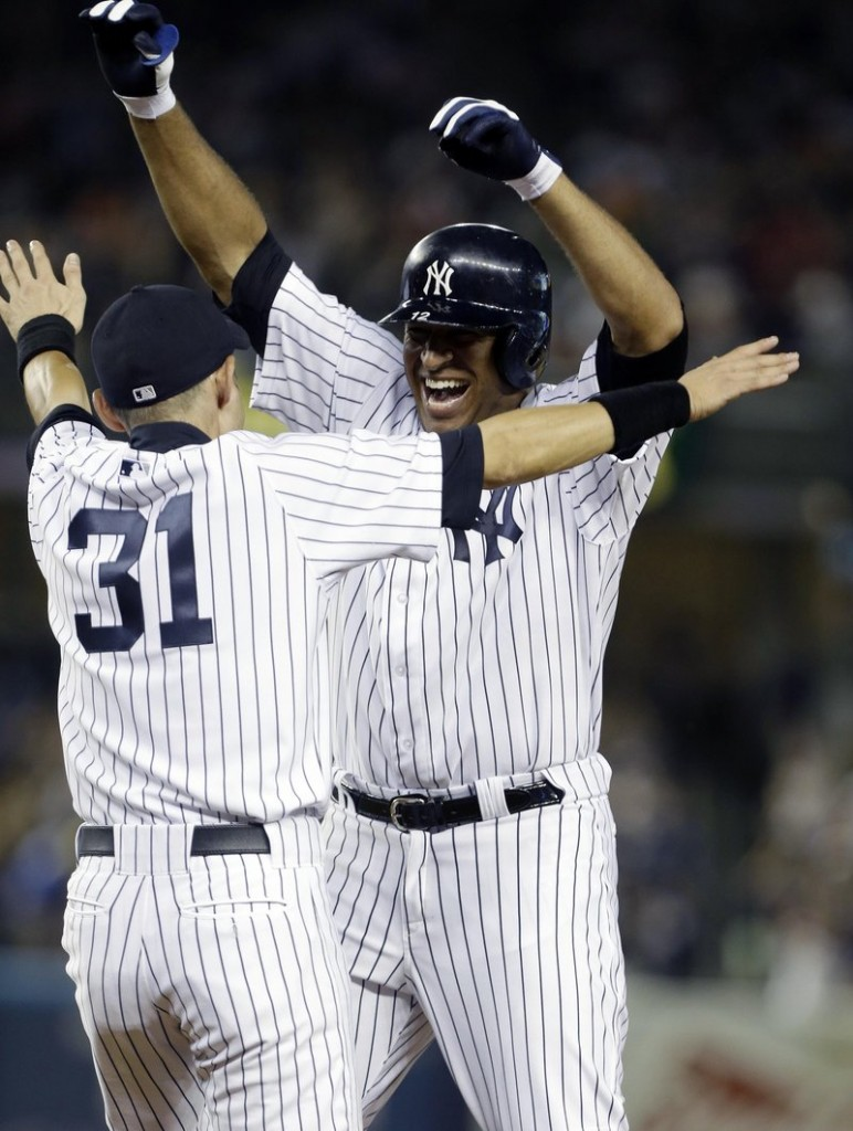 Vernon Wells, right, celebrates with Ichiro Suzuki after hitting an RBI single in the ninth inning Friday night to give the Yankees a 3-2 home win over the Orioles.