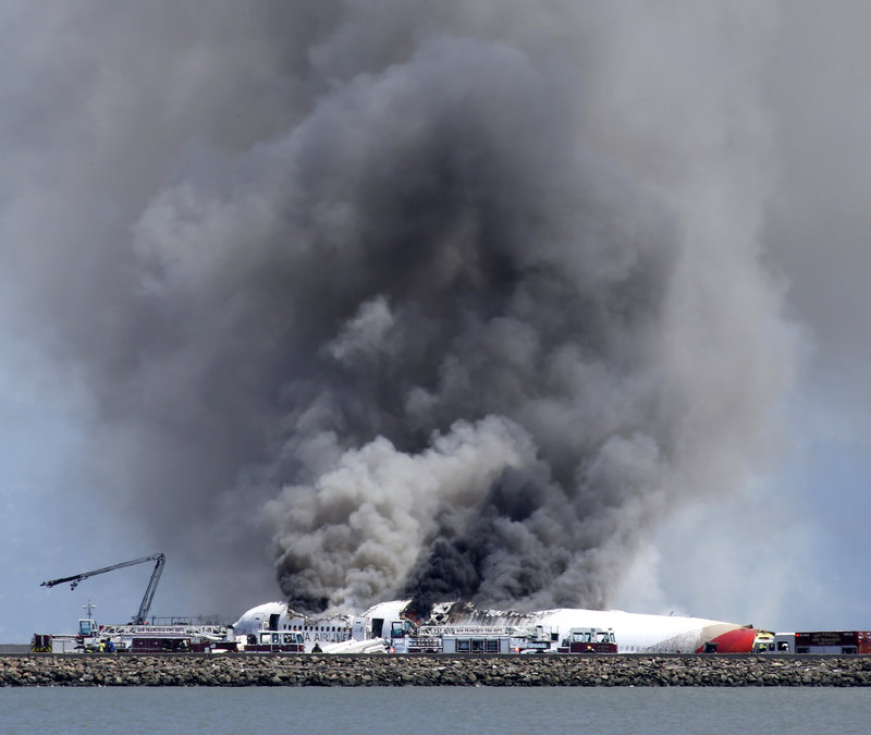 Smoke billows from the crashed Asiana Flight 214 at San Francisco International Airport on Saturday. The cause of the crash is under investigation, and terrorism has been ruled out.