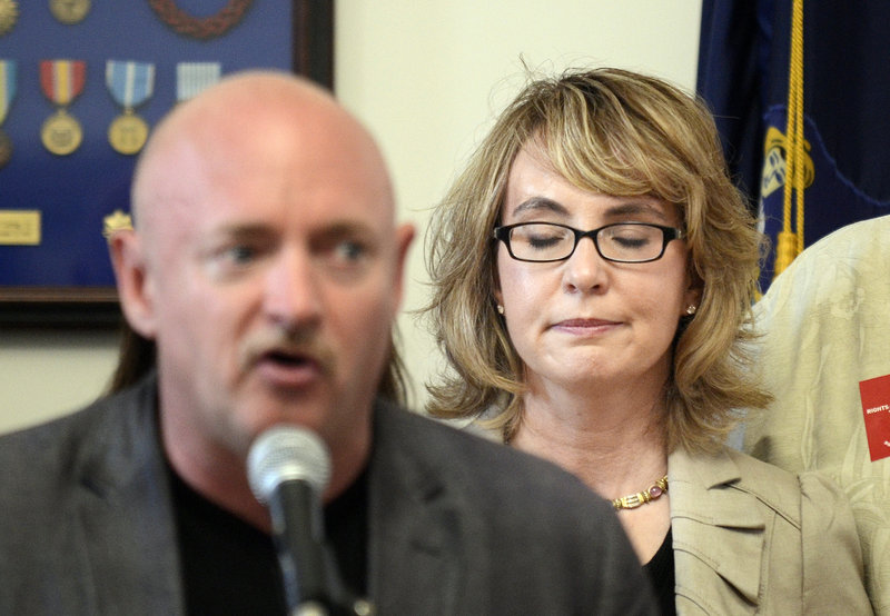 Former U.S. Rep. Gabrielle Giffords listens as her husband, Capt. Mark Kelly, describes the day Giffords was shot in 2011. The couple seek tougher gun-purchasing laws.