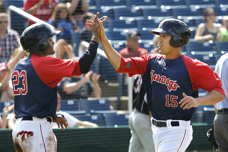 Sea Dogs Tony Thomas, left, and Derrik Gibson celebrate after scoring the tying and go-ahead runs on Shannon Wilkerson's two-out single in the eighth inning of Portland's 4-3 win over New Britain.