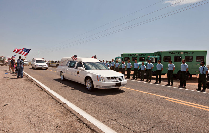 Hearses carrying the bodies of 19 Granite Mountain Hotshots move Sunday past Bureau of Land Management and U.S. Forest Service personnel on the way from Phoenix to Prescott, Ariz. A memorial service is set for Tuesday in Prescott, then funerals will be held for the men.