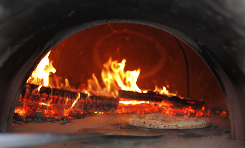 A pizza cooks in an oven at Jillyanna's.