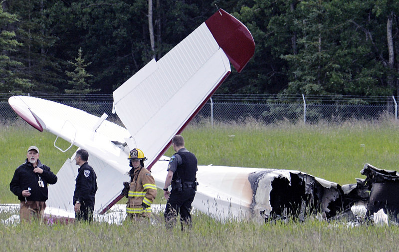Emergency personnel stand near the wreckage of a fixed-wing aircraft that crashed Sunday at the Soldotna Airport in Soldotna, Alaska.