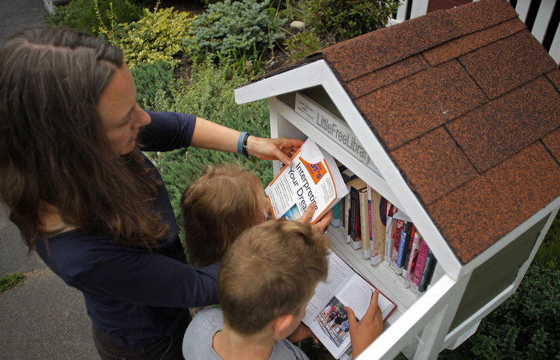 Julie Falatko and her children, 3-year-old Ramona and 7-year-old Eli, rearrange books in their Little Free Library in front of their South Portland home.