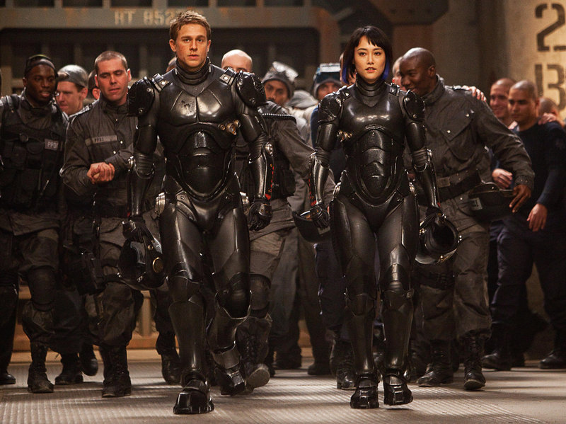 "Charlie Hunnam and Rinko Kikuchi pilot a huge robot in the war against creatures from under the ocean in ""Pacific Rim."""