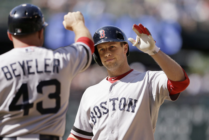 Boston's Daniel Nava, right, is congratulated by first-base coach Arnie Beyeler after hitting an RBI single in the 10th inning to give the Red Sox an 8-7 win over the Mariners.