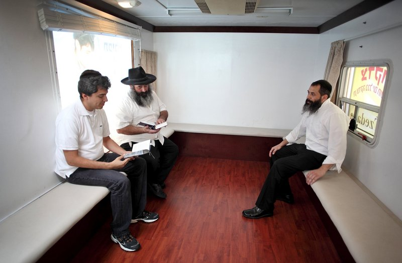 Volunteer Abraham Rosen, center, reads next to Ronen Corcie, left, and volunteer Adan Ogen inside the mitzvah tank. The vehicles seek to engage people who might be avoiding religion.