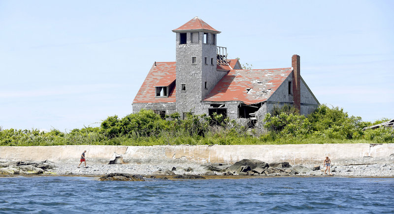 Roger Troudeau of Belgium, left, walks on Wood Island with his daughter Kate. The Wood Island Life Saving Station behind them was built in 1908 and staffed by civil servants who watched for ships in distress near Portsmouth Harbor.