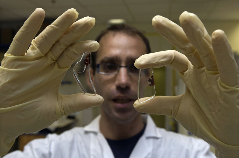 A scientist displays two DNA samples at a lab in Tel Aviv. Intensive DNA collection is taking place around the world, but relatively little debate is taking place over the ethical questions that are likely to arise.
