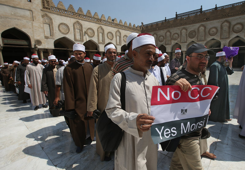 An Egyptian cleric and a supporter of ousted Egypt's President Mohammed Morsi hold up a placard against Egyptian Defense Minister General Abdel-Fattah el-Sissi.