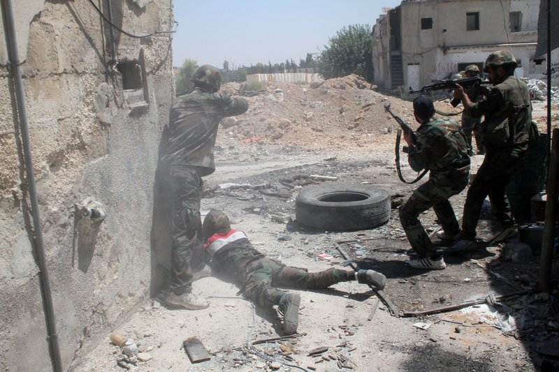 Syrian army personnel shoot toward rebel fighters Sunday during a tour for journalists organized by the Syrian Information Ministry in the Damascus suburb of Jobar.