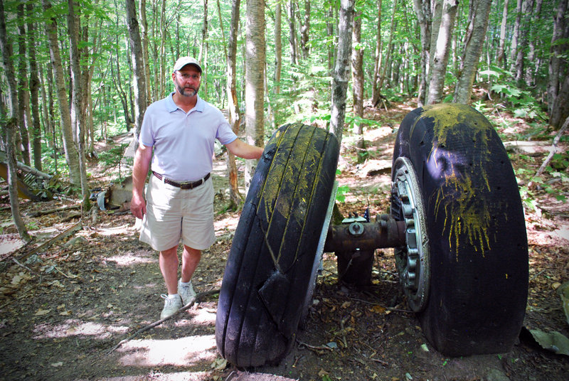 Matt Miller stands by the B-52's tires, part of an enormous swath of debris resulting from the plane crash on Elephant Mountain more than 50 years ago.