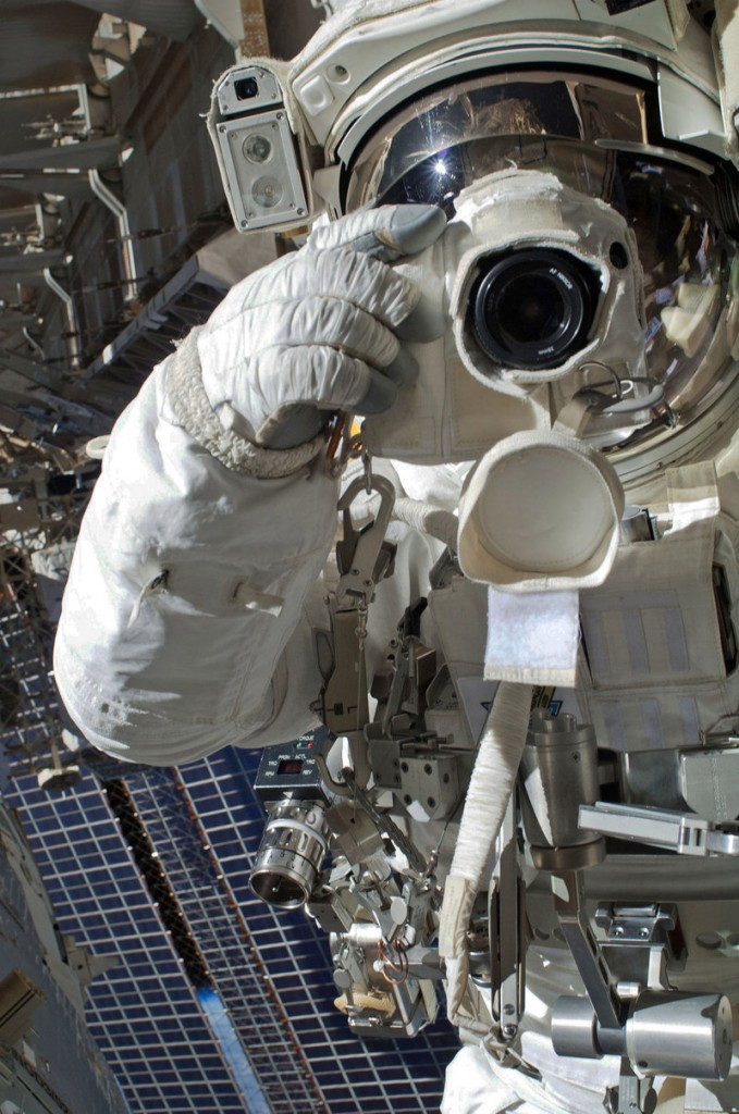 Astronaut Chris Cassidy uses a still camera during a spacewalk Tuesday outside the International Space Station. A short time later, Italian astronaut Luca Parmitano, not in frame, reported an unusual buildup of water inside his helmet and the walk had to be aborted.