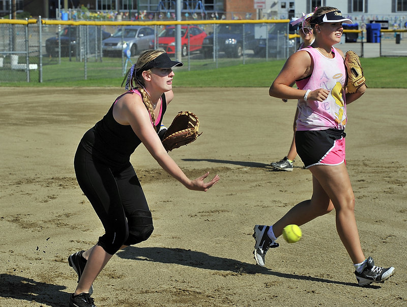 Emilia Wallen makes a low toss to first base during a bunt drill as her teammate and sister, Amanda, also participates with the team of Swedish softball players.