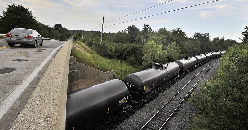 A car passes over the bridge near a line of Petroleum Crude Oil transport rail cars as they sit near Route 115 in Yarmouth on Tuesday, July 23, 2013.