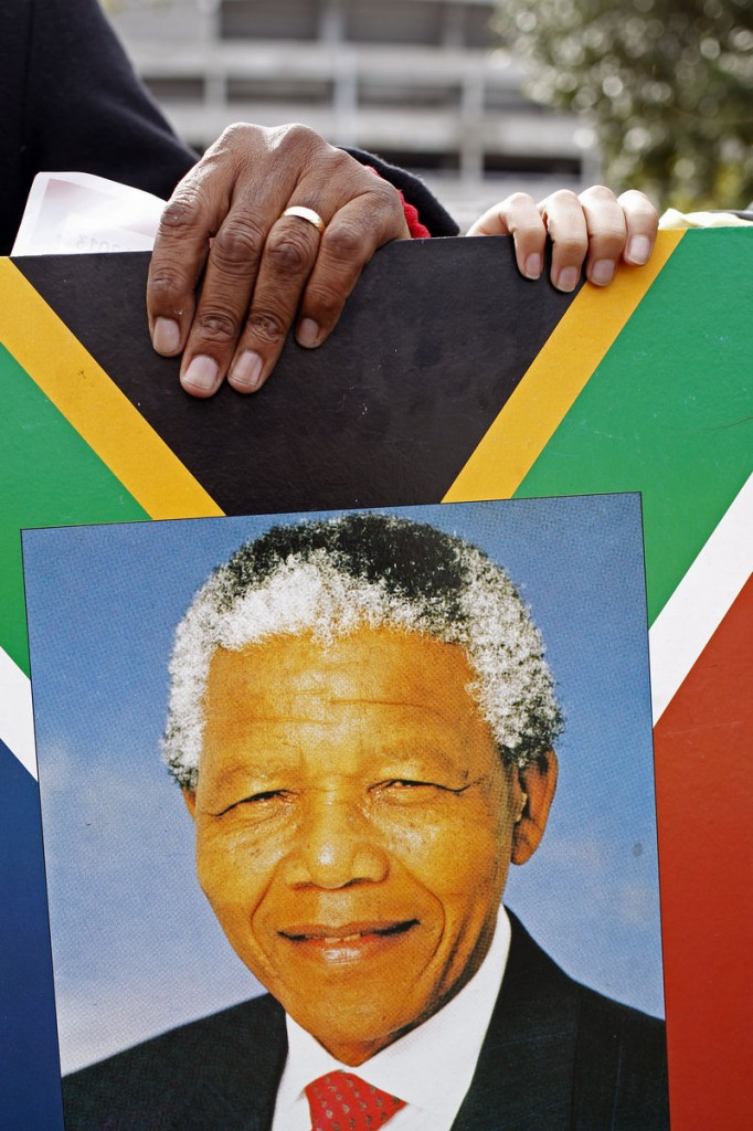 A placard depicting the face of former South African president Nelson Mandela is carried by people honoring his 95th birthday in Cape Town, South Africa, Thursday.