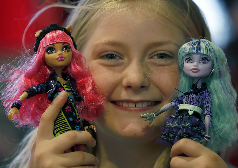 A young girl poses with Monster High dolls, which have grown to an estimated $500 million in annual sales since debuting in 2010, one of many new dolls challenging the popularity of Barbie, displayed below.