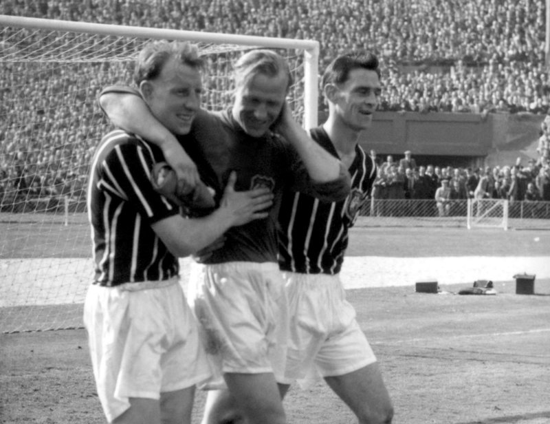 Manchester City's Bert Trautmann, center, is assisted by unidentified players after he helped his team win the May 1956 FA Cup final, despite a broken neck.