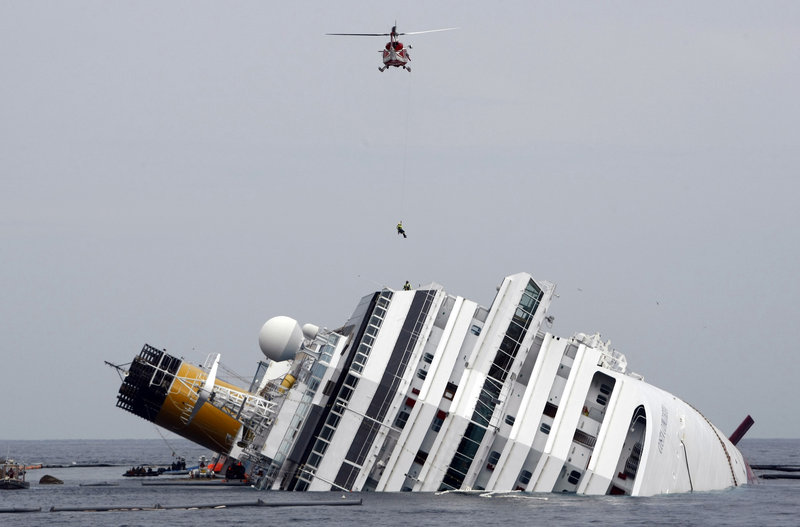 An Italian firefighter is lowered from a helicopter onto the Costa Concordia off Giglio, Italy, on Jan. 31, 2012. The ship's captain was denied a plea bargain and is being tried separately.