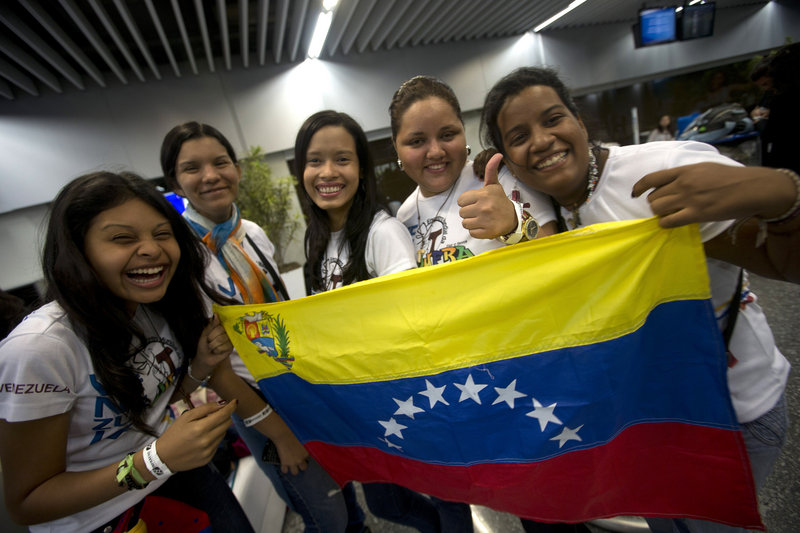 Venezuelans hold a replica of their country's flag after arriving Friday at the international airport in Rio de Janeiro, Brazil. Thousands of young Roman Catholics from around the Americas are converging on the city for World Youth Day and the arrival of Pope Francis, who plans to visit Manguinhos on Monday.