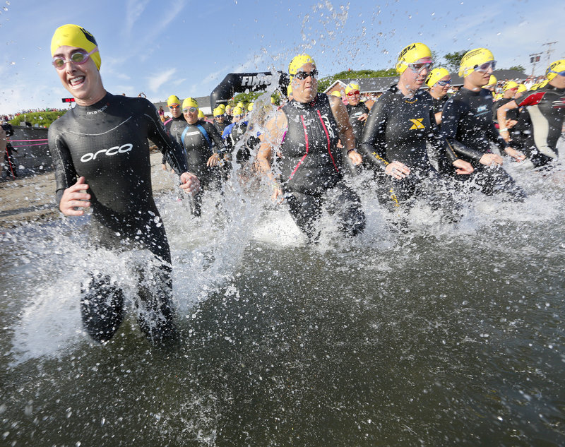 Bernadette Shaw of Cape Elizabeth and others enter the water in the yellow caps group of women ages 35-39 in the Maine Cancer Foundation's Tri for a Cure in South Portland on Sunday. In its sixth year, the event was expected to raise $1.2 million.