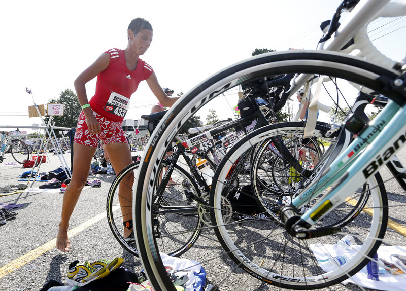 Catherine Corey of South Portland grabs her bike after completing the swim in the Maine Cancer Foundation's Tri for a Cure triathlon in South Portland on Sunday.