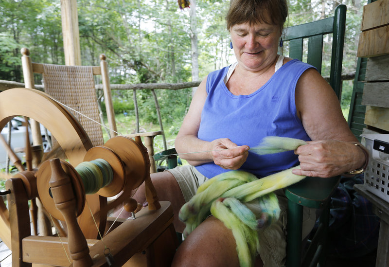 Dedee Montgomery, co-owner of Bessie's Farm Goods in Freeport, spins wool Sunday during Maine Open Farm Day.