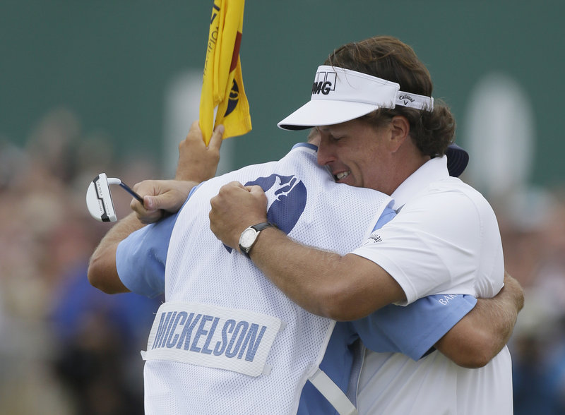 Phil Mickelson embraces his caddy, Jim Mackay, after winning the British Open for the first time on Sunday.