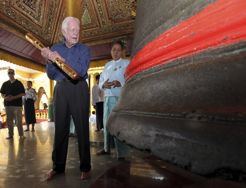 Former President Jimmy Carter prepares to ring a bell during his April 2013 visit to the famed Shwedagon Pagoda in Yangon, Myanmar, formerly known as Burma.