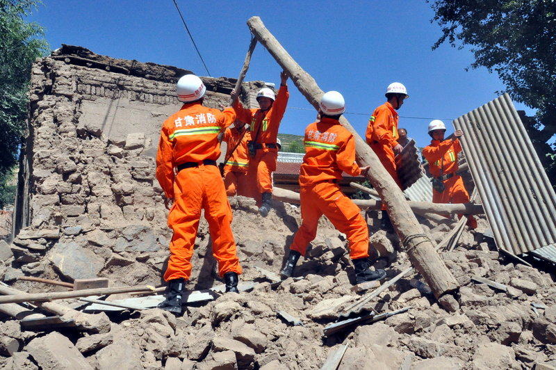 Rescuers clear the debris of a damaged house in the Majiagou village in northwest China's Gansu province after an earthquake struck early Monday morning. The quake's magnitude was estimated at 5.9-6.6.