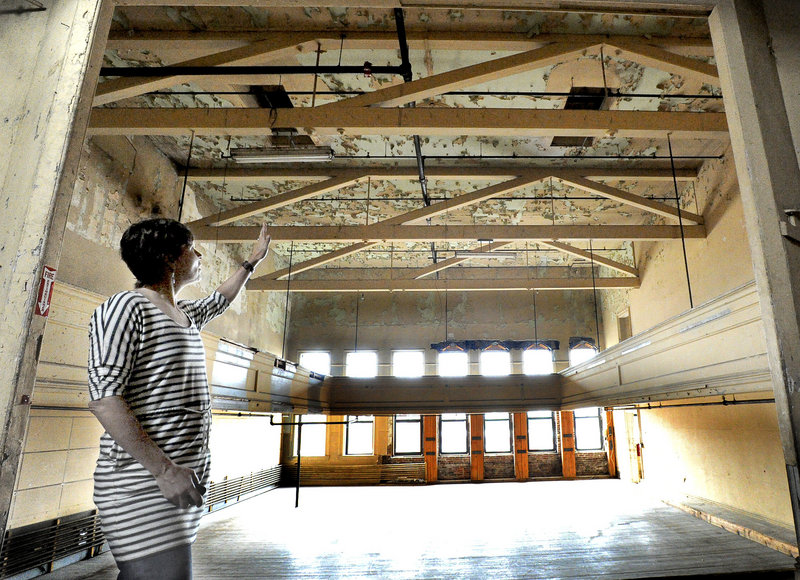 Tammy Ackerman of the nonprofit arts organization Engine is seen here on the third floor of the former Renys store called the Marble Block in downtown Biddeford, where a theater stage and balcony remain.