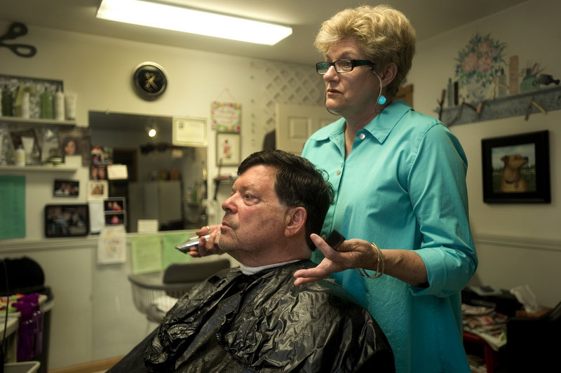 Hairdresser Jane Good of Southport Island talks about the proposed closure of St. Andrews Hospital in Boothbay Harbor with summer resident Walter Weil. Good's salon has become an epicenter of support for keeping the hospital alive in the community.