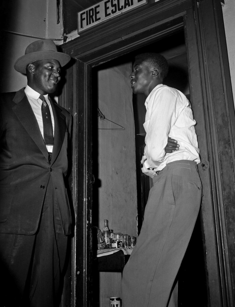 Willie Louis, then known as Willie Reed, right, a witness in the Emmett Till murder case in Mississippi, stands outside his apartment in Chicago, guarded by Detective Sherman Smith in 1955.